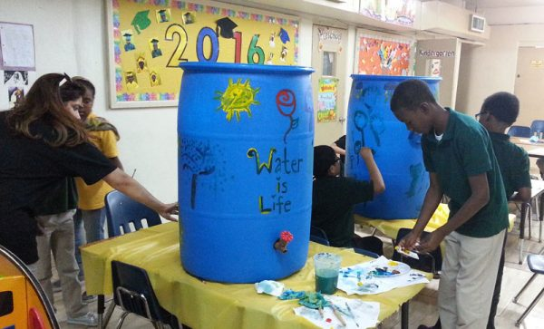 Students painting the rain barrels